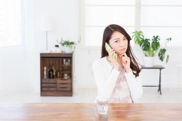 部屋で電話をする女性 考える