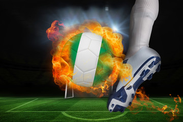 Football player kicking flaming nigeria flag ball against football pitch and goal under spotlights