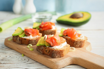 Photo sur Plexiglas Entree Tasty sandwiches with fresh sliced salmon fillet and avocado on wooden board, closeup