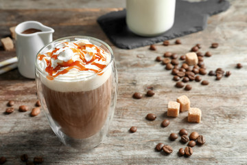 Glass of coffee with caramel topping on wooden background
