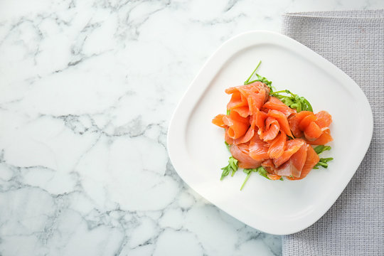 Plate with fresh sliced salmon fillet and arugula on marble background, top view