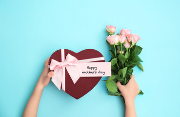 Child holding gift box and flowers for Mother's Day on color background