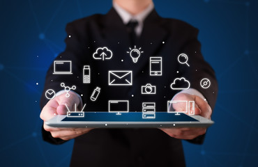 Businessman holding tablet with multimedia icons