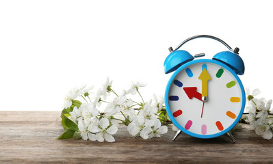 Alarm clock and branch with spring blossoms on wooden table against white background. Time change concept