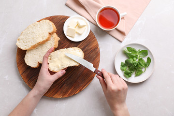 Woman spreading butter on slice of bread over table, closeup