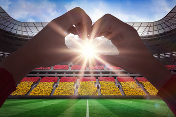 Woman making heart shape with hands against stadium full of germany football fans