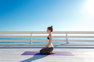 Young slim woman in tight sportswear sitting on purple yoga mat and practicing outdoors at white wooden seafront