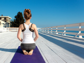Young slim woman in tight sportswear practicing yoga outdoors at white wooden seafront. Back view eith copy space