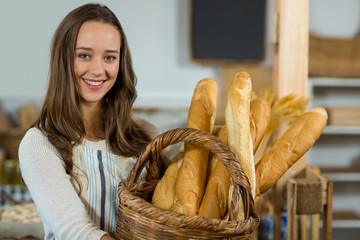 Portrait of smiling female staff holding a basket of baguettes at counter