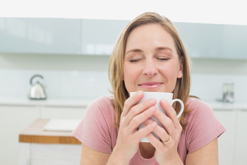 Close-up of a relaxed woman having coffee in kitchen