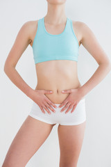 Mid section of a fit woman with hands on belly