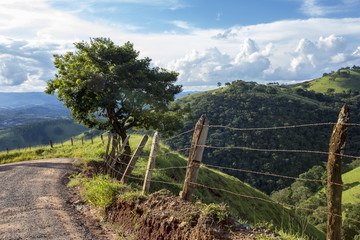 Fence, tree, blue sky and hill on countryside of Brazil