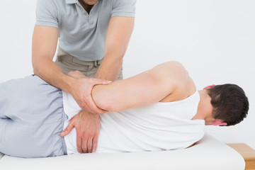 Male physiotherapist examining mans back