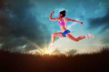 Fit brunette running and jumping against blue sky over grass