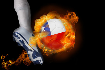 Football player kicking flaming chile ball against black