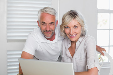 Smiling mature couple using laptop at home