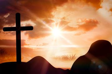 Wooden cross against sunrise over grass
