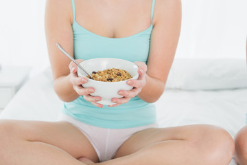 Mid section of a female with a bowl of cereal sitting on bed