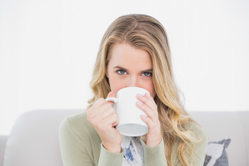 Cute blonde drinking coffee sitting on cosy sofa