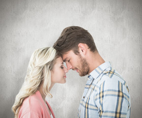 Attractive couple standing touching heads against white background