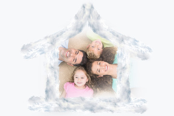 Happy family lying on the rug in a circle against house outline in clouds
