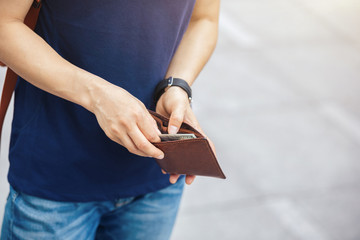 hands taking money out form wallet in the city