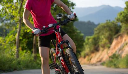 Young woman cycling mountain bike on trail