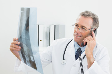 Doctor with xray picture while using telephone at office