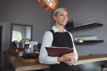 Thoughtful waitress standing with menu card