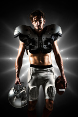 Shirtless American football player with padding holding ball and helmet against spotlight