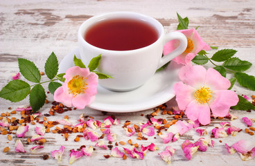 Cup of tea with wild rose flower on rustic wooden background