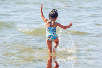 Little girl playing in the waves at the beach