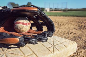 Baseball and glove laying on a base
