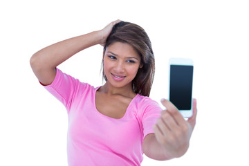 Pretty brunette taking a selfie with smartphone