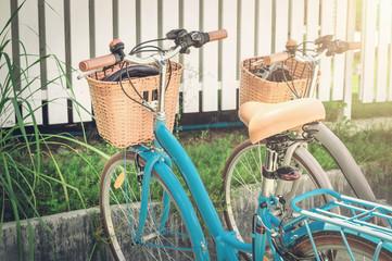 Two retro bikes parked near village white fence
