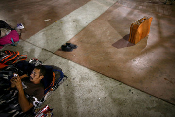 A member of a caravan of migrants from Central America looks at his mobile phone as he prepares to spend the night near the San Ysidro checkpoint in Tijuana