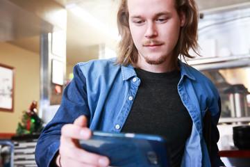 Young man at a restaurant looking at his phone