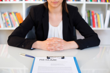 Young woman showing her curriculum resume during job interview