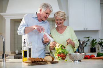 Happy senior couple preparing vegetable salad