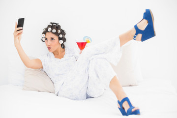 Brunette in hair rollers and wedge shoes having a cocktail taking a selfi