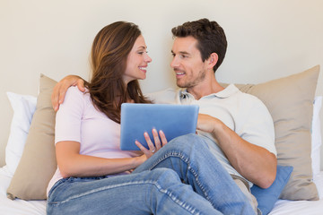 Happy relaxed couple using digital tablet in living room