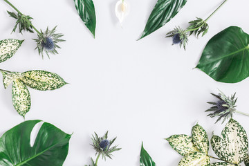 Summer tropical composition. Green tropical palm leaves and flowers on gray background. Summer concept. Flat lay, top view, copy space