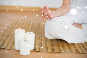 Woman sitting in lotus pose beside white candles against snow
