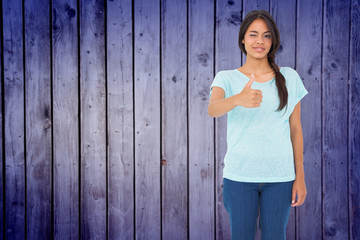 Happy brunette giving thumbs up against wooden planks background