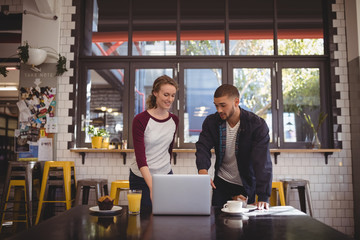Man gesturing at laptop while standing by woman
