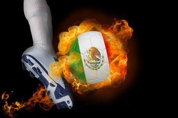 Football player kicking flaming mexico ball against black
