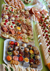 buffet with many trays filled with sweet pastries and sandwiches
