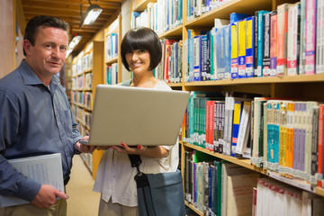 Woman holding laptop with man