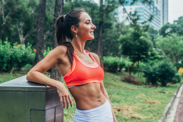 Slim fitness brunette woman with six pack abs wearing pink sport bra standing in city park relaxing after workout looking away from the camera