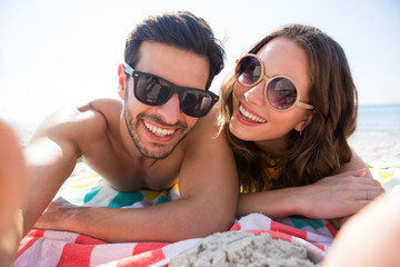 Portrait of happy couple wearing sunglasses while lying together on blanket at beach
